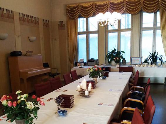 Lahsen NNKY:n juhlasalissa pitkä pöytä ja pöydällä kukkakimput, kynttilät ja virsikirjat