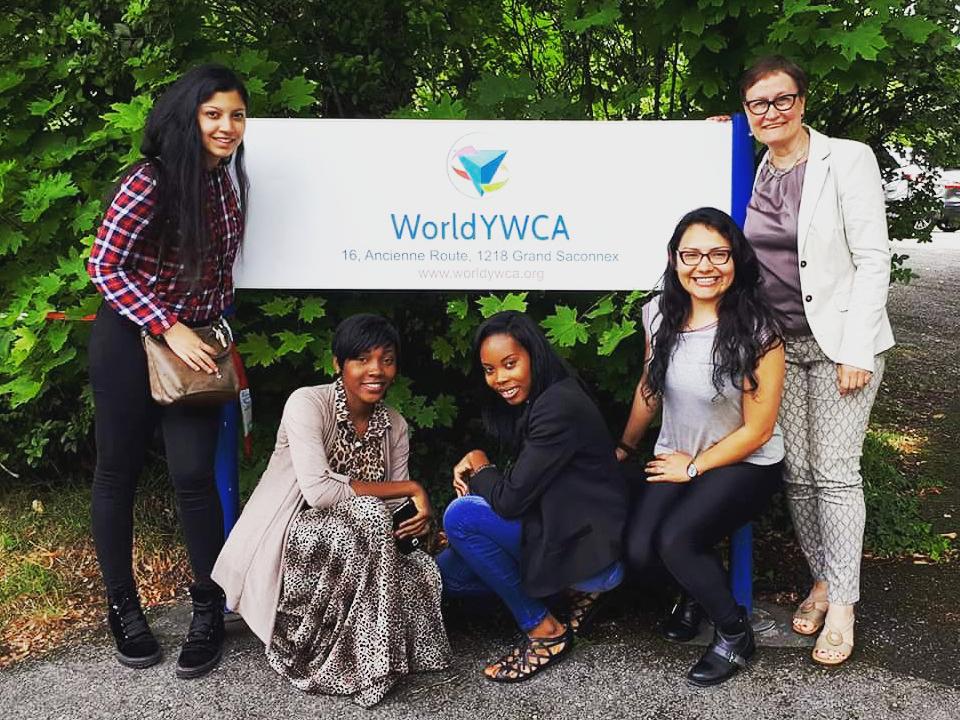 Nuoret naiset pitävät World YWCA-kylttiä