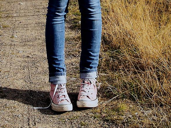 Lapsen tai teinin jalat hiekkatien laidassa, farkut jalassa