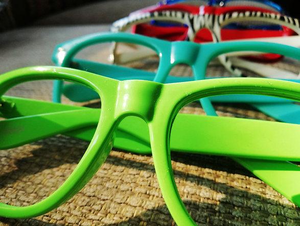 Värikkäät silmälasikehykset pöydällä